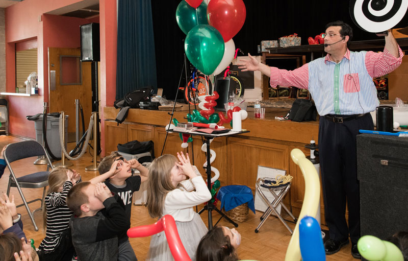 Magician Steven Craig entertaining children at a birthday party in New England