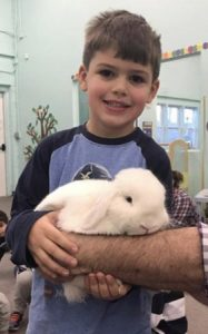 boy holding bunny during birthday party magic show