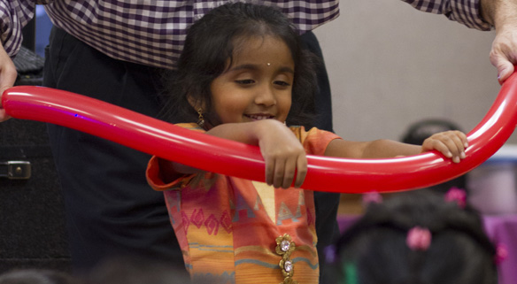 Indian child holding a balloon at a children's birthday party by kids entertainer Steven Craig
