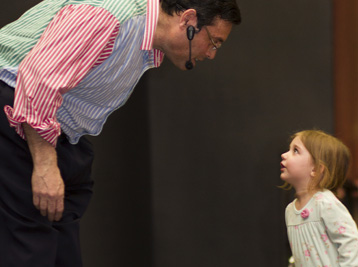 kids entertainer Steven Craig talking with little girl during a children's magic show