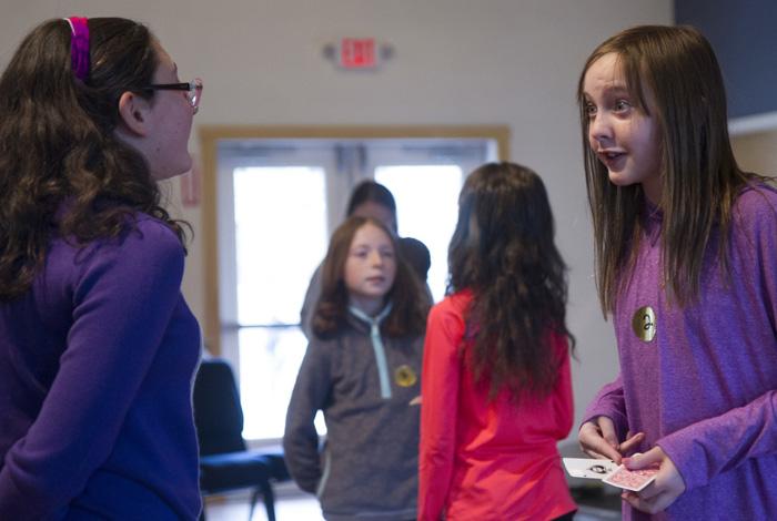 two girls learning a magic trick at Steven Craig's magic workshop